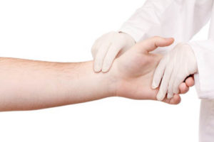 Nurse wearing gloves i in physical contact with patient in isolation.